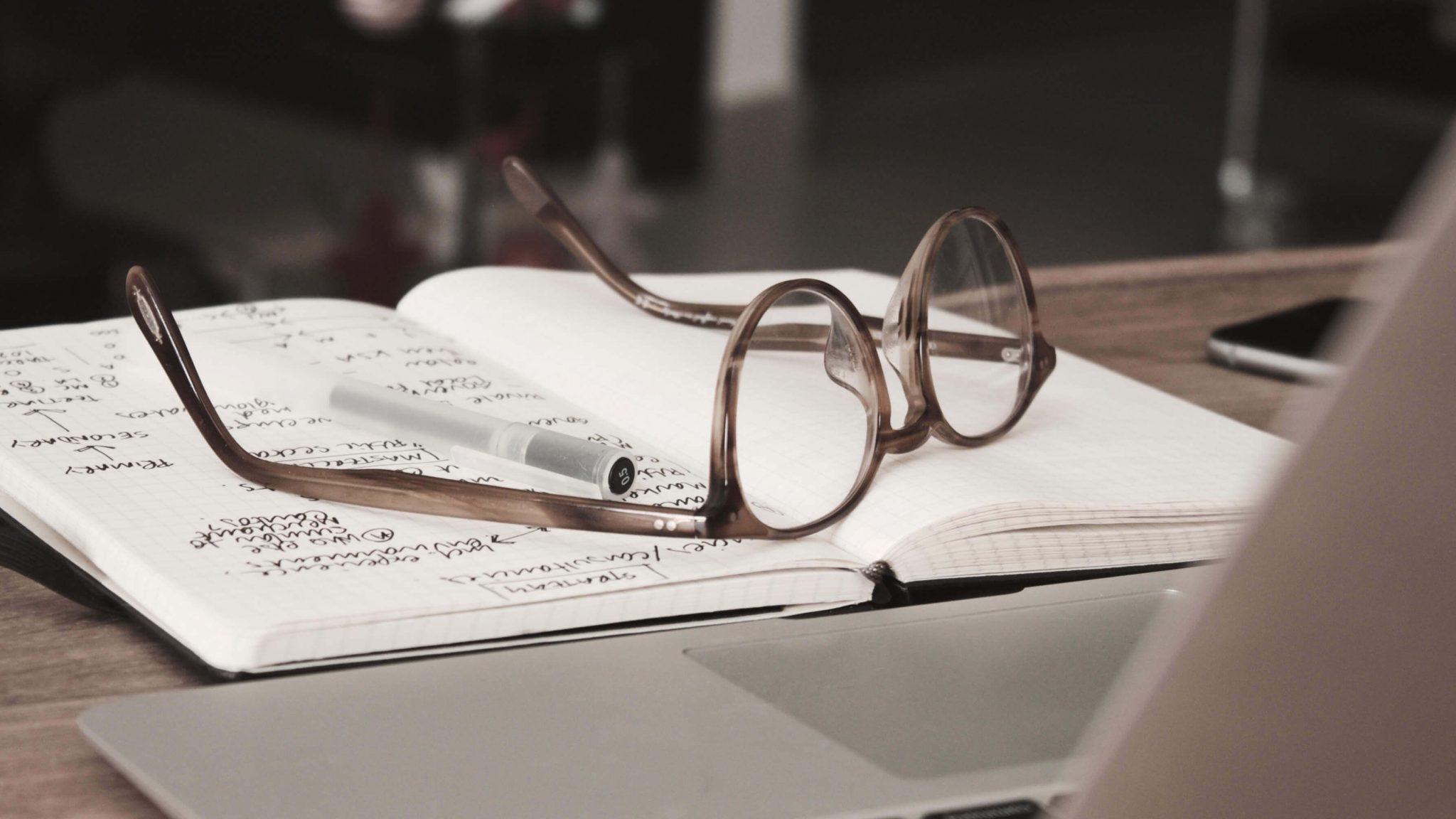 Die Brille eines Lektors liegt auf einem Buch