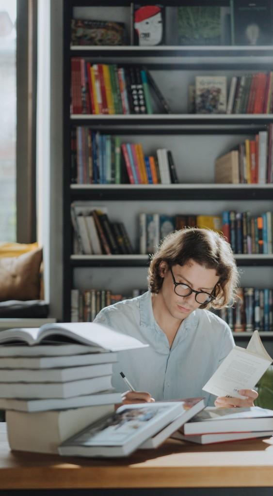 Ein junger Lektor mit Brille liest in einem Buch