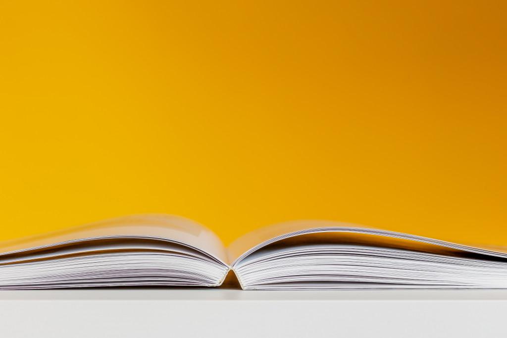Aufgeschlagenes Buch vor gelbem Hintergrund