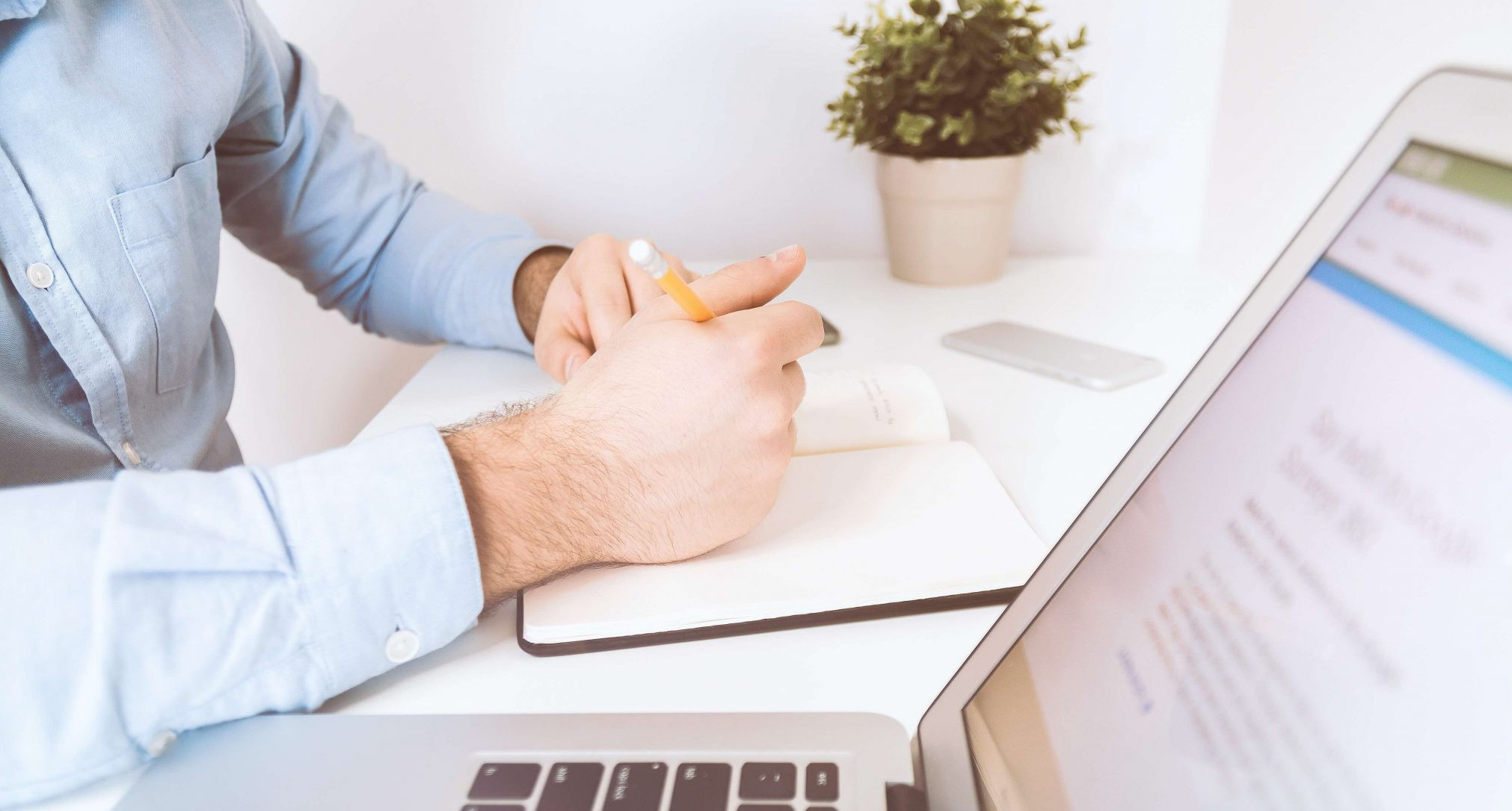 Mann lernt mit Notizbuch vor Laptop