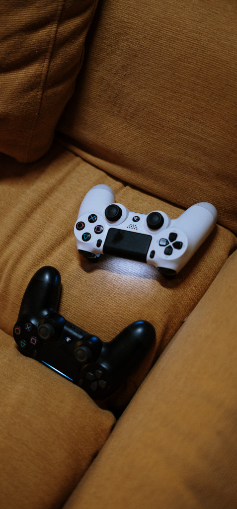 2 Controller liegen auf einem Sofa