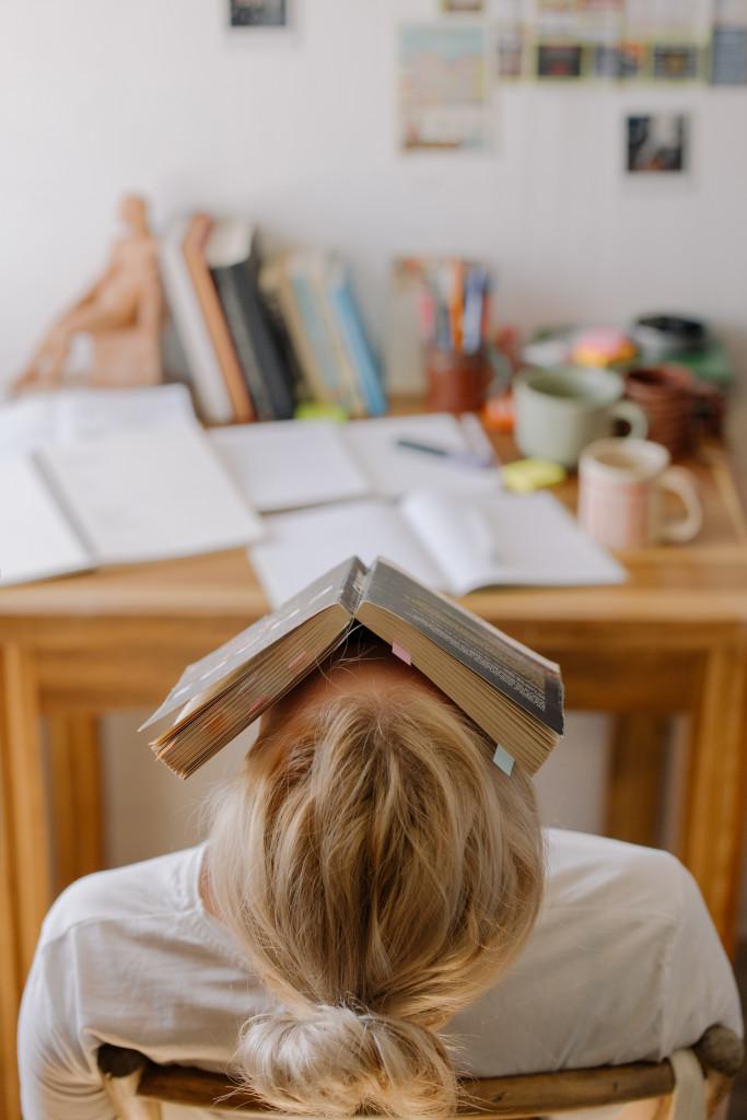 Frau chillt mit Buch auf den Kopf