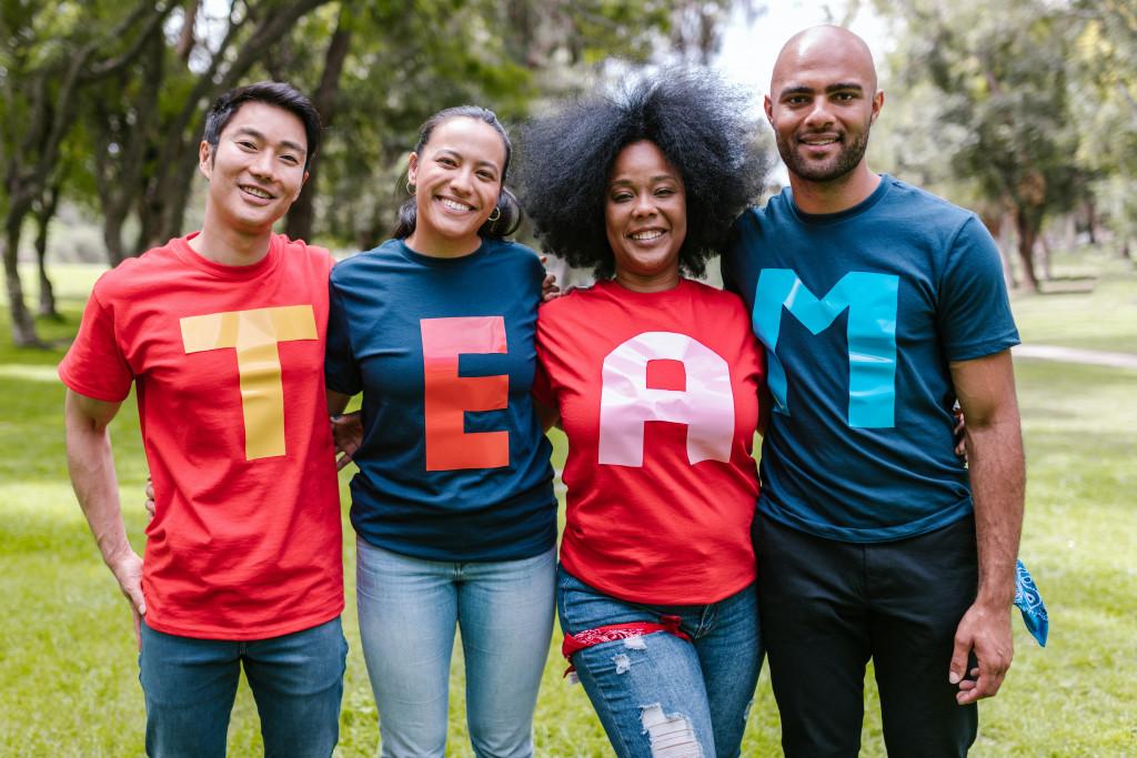 Personen mit Buchstaben auf den Shirts