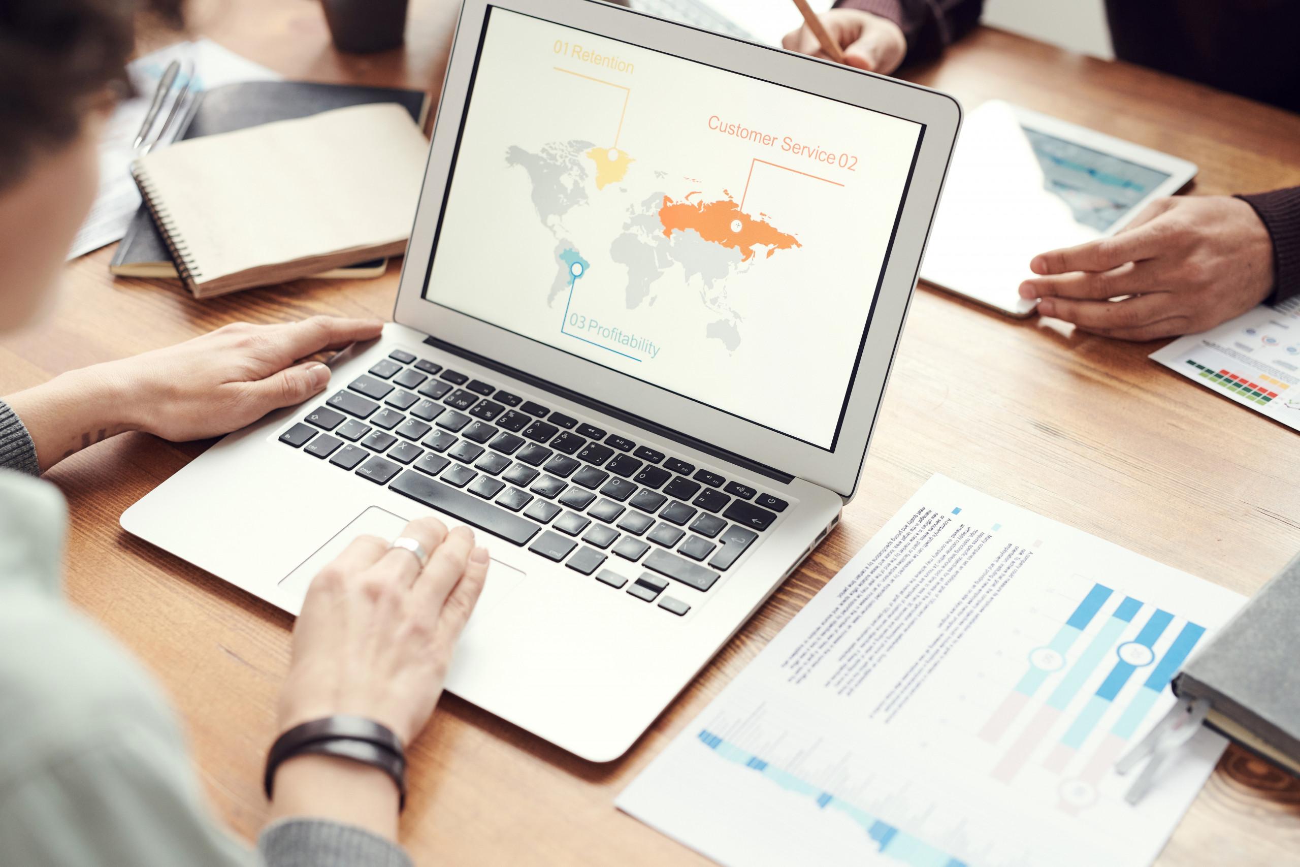 Jemand erarbeitet eine internationale Strategie am Laptop