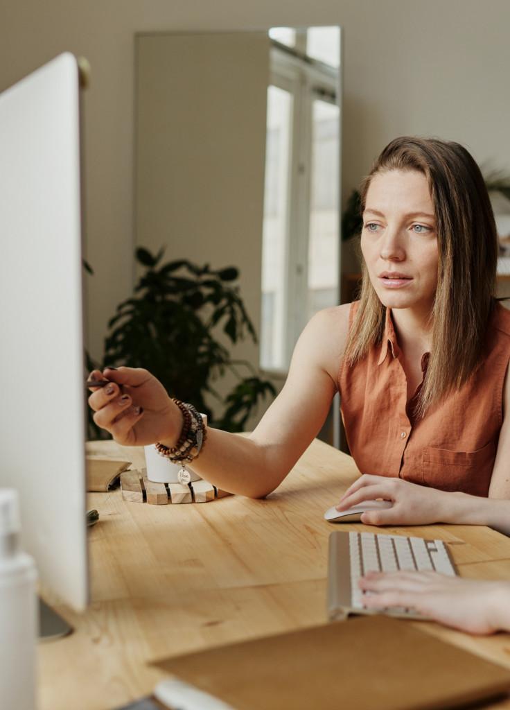 Eine Frau zeigt etwas auf einem Computer-Bildschirm