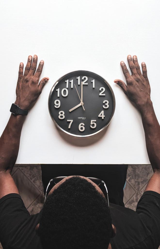 Ein Mann sitzt vor einer Uhr