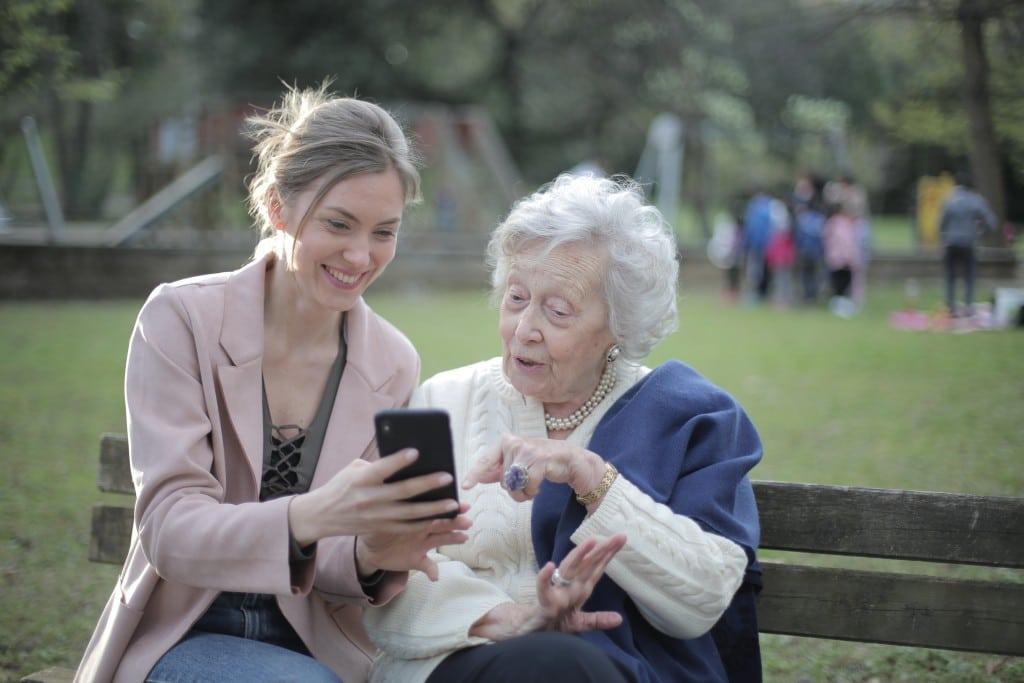 Enkelin sitzt mit Großmutter im Park und sieht sich was am Smartphone an