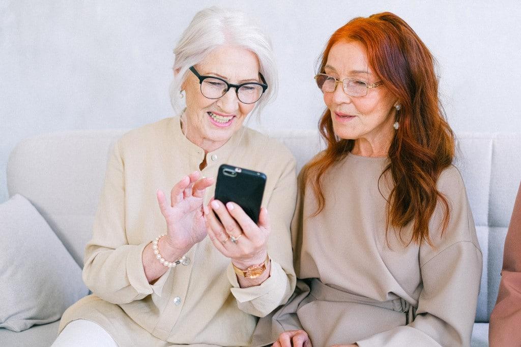 Zwei Seniorinnen sehen etwas auf dem Mobiltelefon an