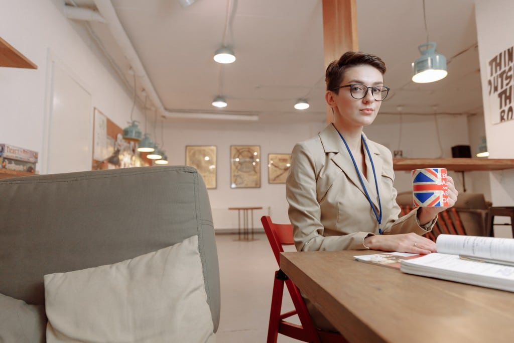 Eine junge Frau sitzt am Tisch mit einer Tasse Kaffee, auf der Tasse ist die England-Flagge