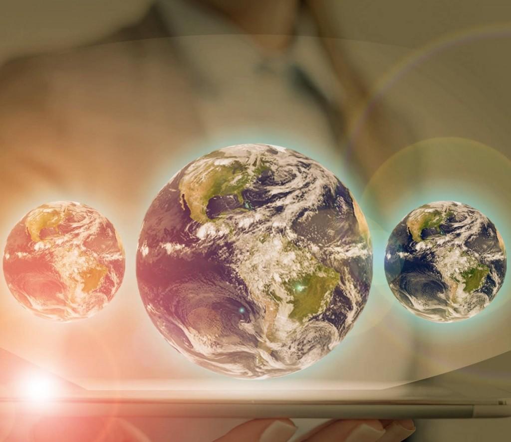 Ein Mann hält ein Tablet in der Hand und darüber schweben drei Globusse