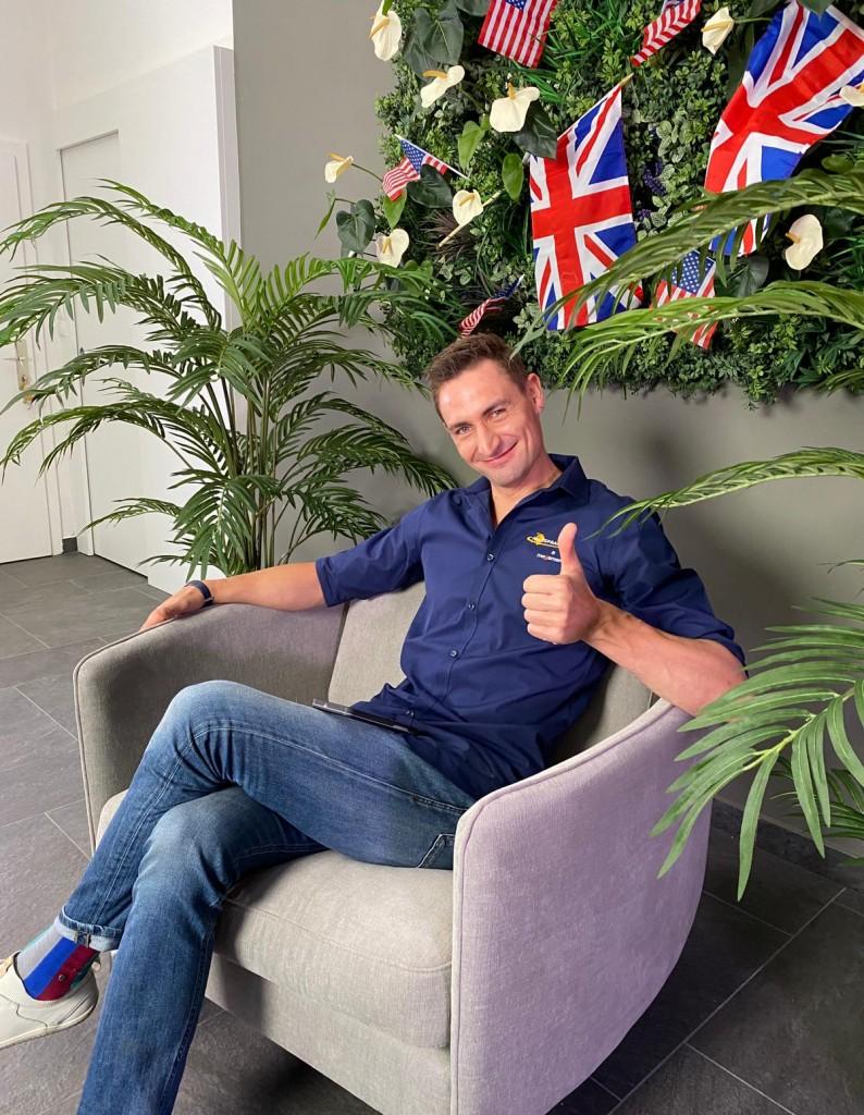 Ein Brite sitzt auf einem Stuhl und hält den Daumen hoch