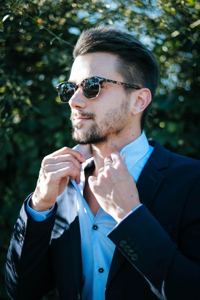Ein Geschäftsmann mit Sonnenbrille richtet den Kragen seines Hemdes