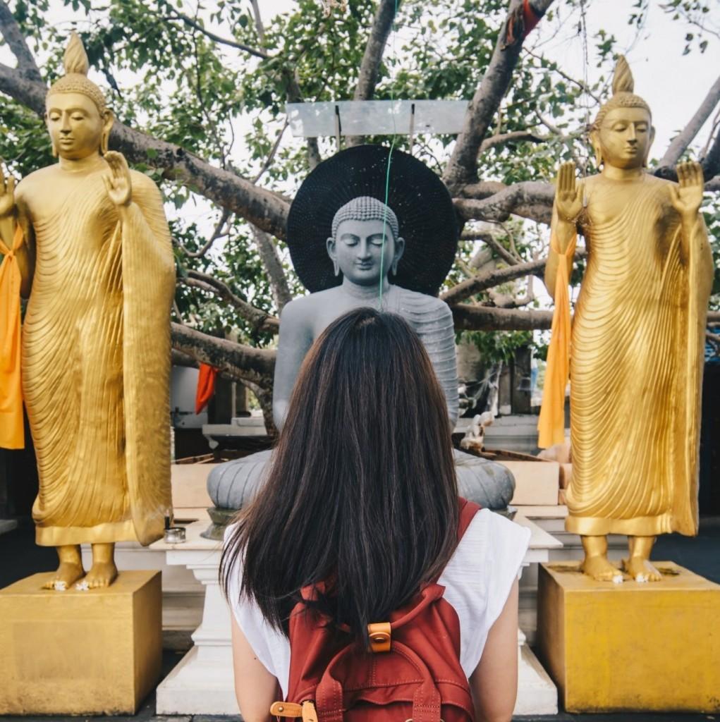Eine Touristin steht vor indischen Statuen