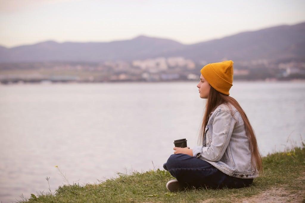 Eine junge Frau mit einer Mütze sitzt an einem See und denkt nach