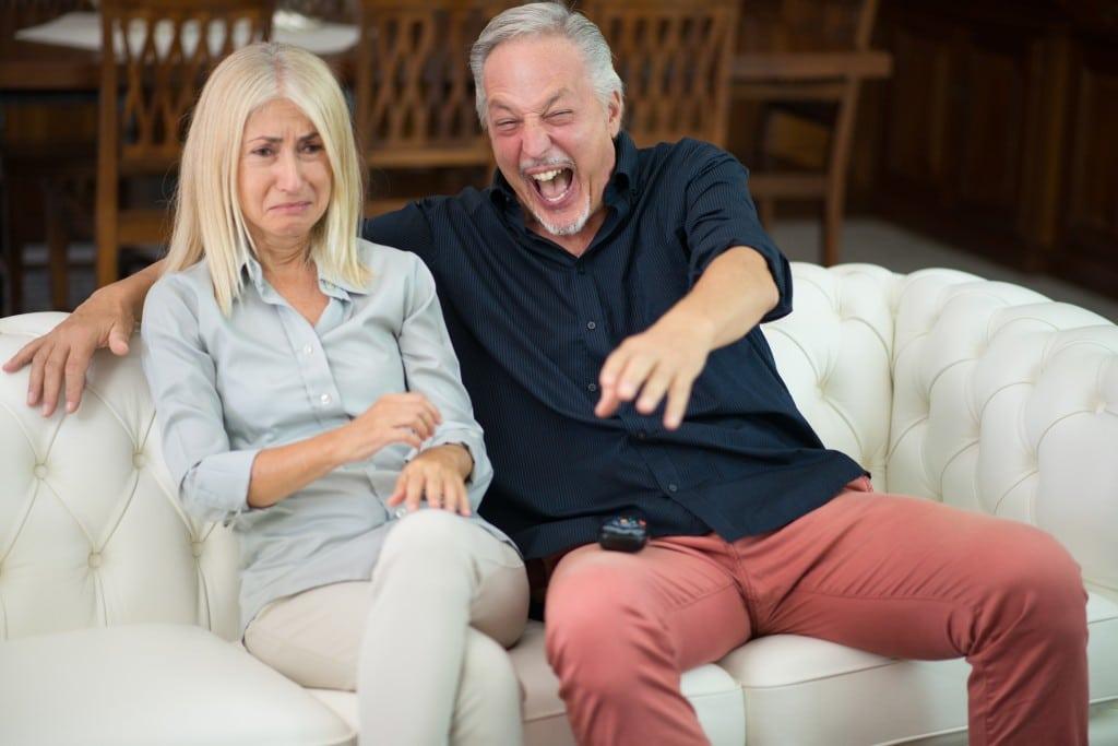 Eine weinende Frau und ein lachender Mann sitzen auf einem Sofa.