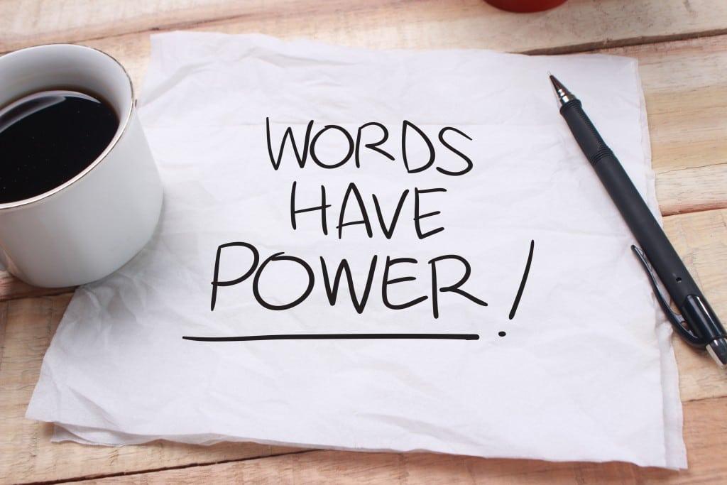 Ein Blatt Papier mit der Aufschrift Words Have Power! Daruf liegt ein schwarzer Kugelschreiber und links davon steht eine Tasse Kaffee