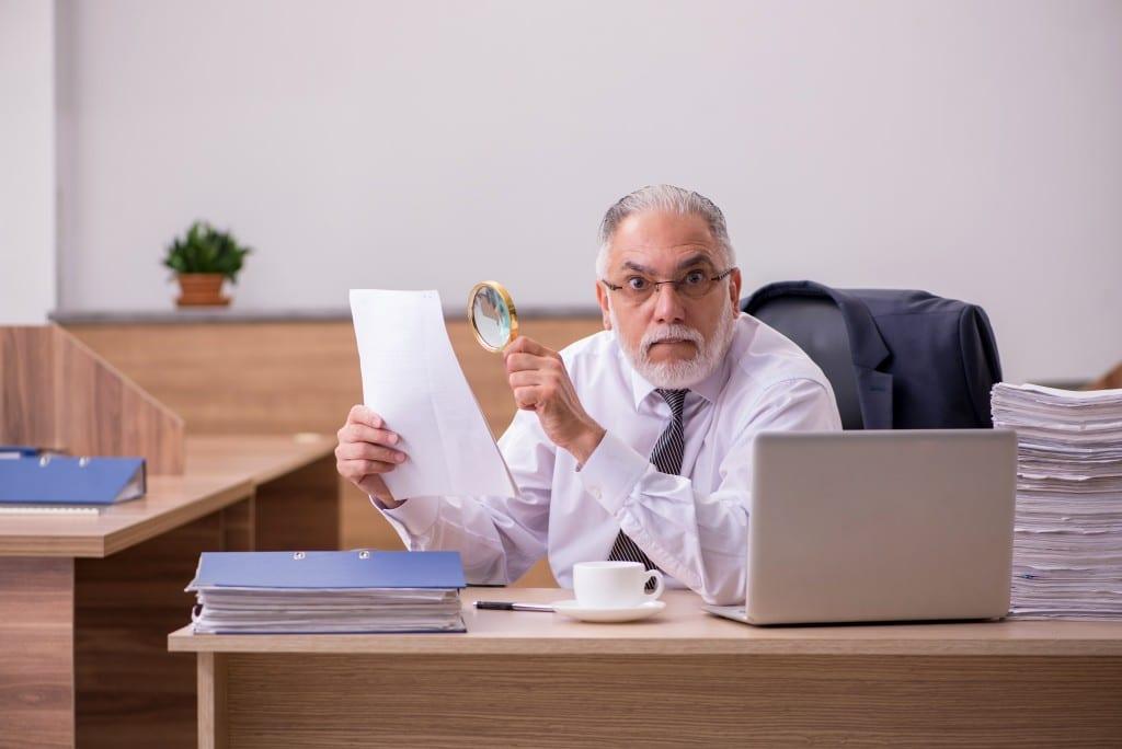 Ein älterer Mann sitzt vor einem Notebook und sieht sich mit einer Lupe ein Dokument an.