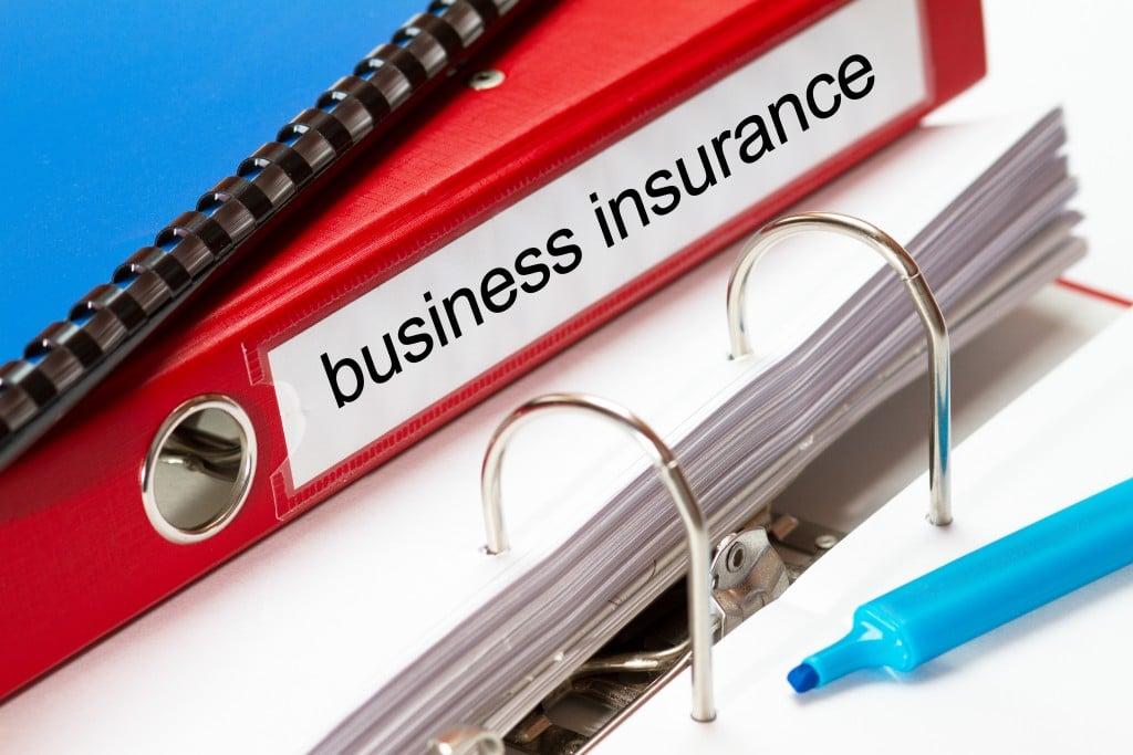 Ordner übereinandergelegt, auf dem roten Ordner steht business insurance